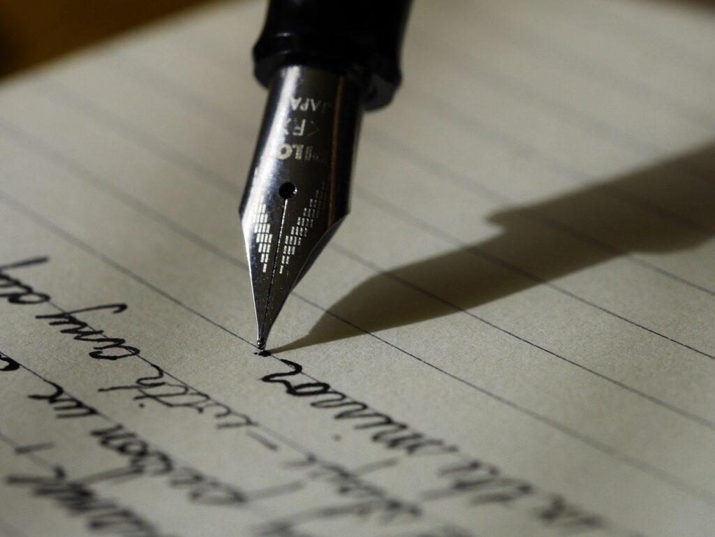 Imagen de una pluma escribiendo en un papel antiguo